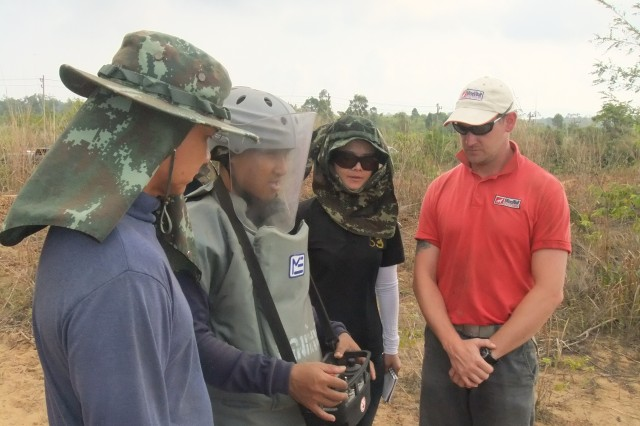 A MineWolf representative helps train a Thailand Mine Action Center employee during a CERDEC NVESD Humanitarian Demining Research & Development program Operational Field Evaluation of the Mini MineWolf landmine clearing system.