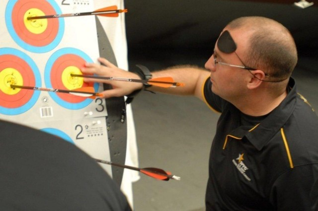 Spc. Jon B. Brancheau, a National Guard infantryman from Grand Rapids, Mich., currently assigned to the Warrior Transition Unit in Fort Bliss, Texas, checks his target for scoring during archery practice at Fort Carson, Colo.  Brancheau and nearly 200 other injured, ill or wounded athletes from four of the military branches as well as a team from the United Kingdom are competing in the fourth Annual Warrior Games May 11-16.