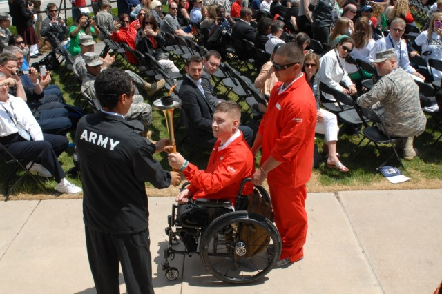 COLORADO SPRINGS, Colo.  -  Army Spc. (Ret.) Luis Puertas, from Orlando, Fla., passes the torch to Marine Pfc. Artem Lazukin during the opening ceremonies at the Warrior Games held at the Olympic Training Center in Colorado Springs, Colo. on May 11, 2013.  Hundreds were on hand for the ceremony, including Great Britain's Prince Harry.  (Photo by U.S. Army Staff Sgt. Brent Powell, 210th Mobile Public Affairs Detachment)