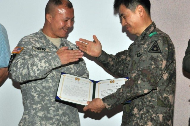 Lt. Col. Park Ju Hyun, commander for Area II ROK Army Support Group, presents the certificate of appreciation to Capt. Eddie L. Novo who directed the 2013 KATUSA & U.S. Soldier Friendship Week during the appreciation ceremony held at R&R Bar and Grill, May 14. (U.S. Army photo by Pfc. Lim Hong-seo)