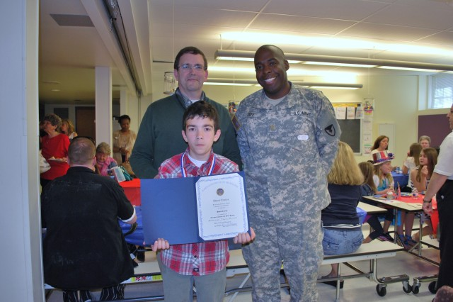 Pascal Conroy (front) displays his Patriot Day certificate as his proud father Paul and Maj. Jason Tate, both from WMRD, pose for a group photo.
