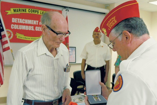 James Lett, left, is presented with the Medal in Commemoration of Victory in the Resistance Against Aggression by Robert King, commandant of the Columbus detachment of the Marine Corps League, Saturday during the detachment's meeting. Lett earned the medal during World War II, but did not receive it until Saturday.