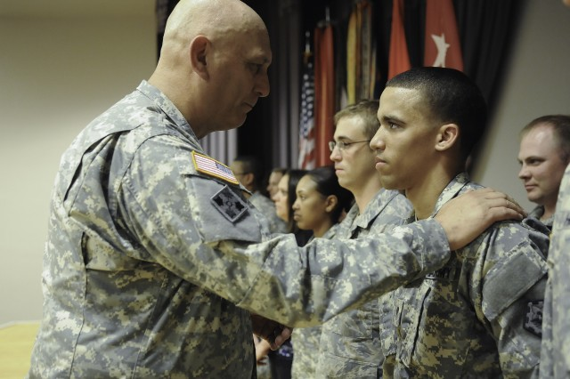 "Army Chief of Staff Gen. Raymond Odierno congratulates Spc. Joshua Newbury, with the 111th Sapper Company, 70th Engineer Battalion, 1st Armored Brigade Combat Team, 1st Infantry Division ""Big Red One,"" after giving him a coin, May 14, 2013, at Fort Riley, Kan. Newbury was among the Fort Riley Soldiers, civilians and airman recognized by Odierno following a community town hall at Barlow Theater. Newbury stood out among his peers and was the first person in 10 years to fire a live mine-clearing line charge towed behind a Husky during a combined arms breach at the National Training Center in California."