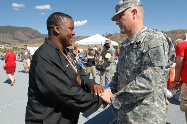 """Sgt. Maj. of the Army Raymond F. Chandler III awards a track and field gold Sgt. Monica Southall on May 14, 2013 during the 2013 Wounded Warrior Games at the Air Force Academy in Colorado Springs, Colo.Southall won gold medals in the standing discus and standing shot put. Chandler and his wife spent the day on Tuesday meeting, encouraging and speaking to athletes taking part in various events. Southall said she appreciates the support of the Army's highest enlisted NCO.""""It speaks volume to have him out here supporting us. We need all the support we can get. Leadership being out here shows us how much they support us,""""Southall said."""