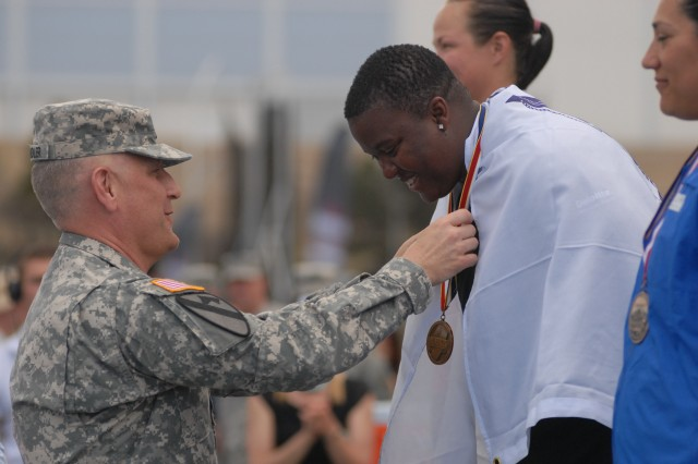"""Sgt. Maj. of the Army Raymond F. Chandler III awarded Sgt. Monica Southall her track and field gold medal on May 14, 2013 during the 2013 Wounded Warrior Games at the Air Force Academy in Colorado Springs, Colo. Southall won gold medals in the standing discus and standing shot put.""""It feels great to have won two gold medals this year. I worked hard. I'm glad it paid off,"""" Southall said."""
