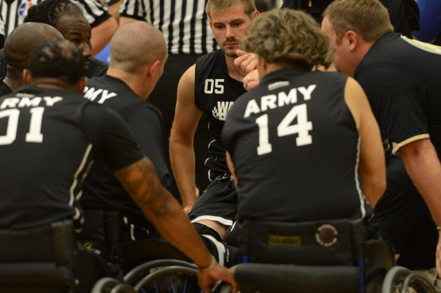 Soldiers on the wheelchair basketball team have a team huddle and moment of esprit during a break in a game.