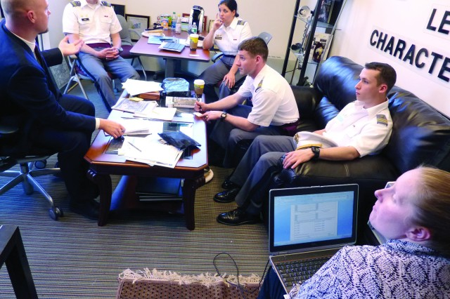 "U.S. Military Academy cadets prepare to fill out disclosure paperwork for their ""40mm Non-Destructive Windshield Obstruction"" senior project as Jeffery Lukaszyk briefs them on patents and Andrea Stevens captures necessary information on her laptop computer."