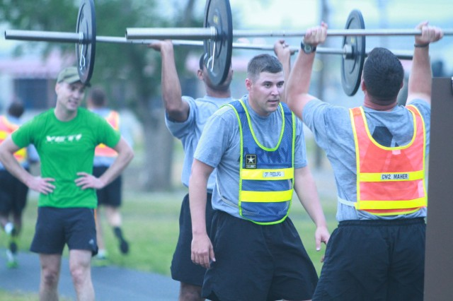 Air Defense Artillery's Captains Career Course students do clean and presses, part of a CrossFit workout May 9 at Graham Resiliency Training Center. It was one of 10 stations they did. In between each station they ran a lap on the track. Their APFT scores have increased since starting the workouts, and they credit it with the challenging exercises.