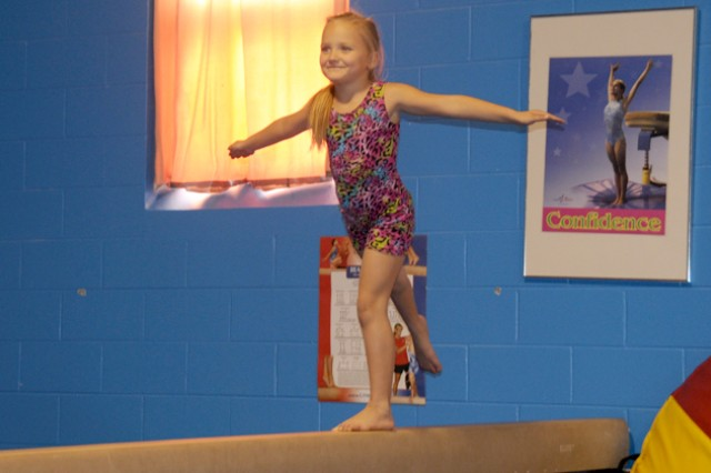 Emily Anderson, 6, practices gymnastics on the balance beam during her lesson May 10 at the school age center.