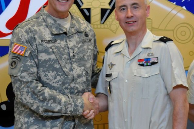 FORT BRAGG, N.C. (May 16, 2013) - Maj. Gen. John R. O'Connor (left) poses with French Army General de Brigade Jean-Yves Lauzier at the Army emblem on display in the Marshall Hall headquarters of U.S. Army Forces Command here today.  Lauzier, logistics deputy of the French Army Land Forces Command, is visiting Fort Bragg to discuss military sustainment topics with FORSCOM, XVIII Airborne Corps and the 82nd Airborne Division.  The visit also includes virtual trainer and parachute rigging demonstrations. O'Connor is the FORSCOM deputy chief of staff, G4, who hosted the visit.