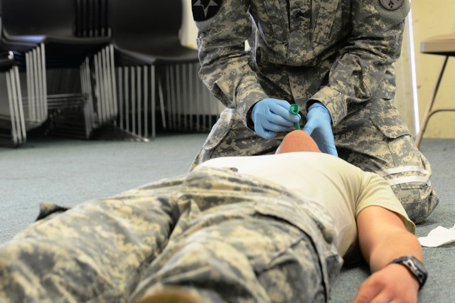 Sgt. Stephen Yang, a senior medic with U.S. Army Pacific, Headquarters and Headquarters Battalion, Headquarters Support Company, demonstrates a nasopharyngeal airway procedure on Spc. Nathan West during a combat lifesaver recertification course at Fort Shafter, Hawaii, 10 May.  Yang said it was important for all Soldiers to know these life saving skills.