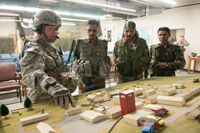 U.S. Army Lt. Col. Phillip Sounia, commander of 3rd Squadron, 73rd Cavalry Regiment, 1st Brigade Combat Team, 82nd Airborne Division, describes a scale model of a training area to Indian Army Brig. Gen. Jagdish Chaudhari, commander of the 99th Mountain Brigade, Col. Prashant Kandpal, commander of 2nd Battalion, 5th Gurkha Rifles, and his executive officer, Maj. Arun Varughese prior to company-level training May 13, 2013, at Fort Bragg, N.C.  They are participating in Yudh Abhyas, an annual bilateral training exercise between the Indian Army and United States Army Pacific, hosted this year by the 82nd Airborne Division's parent organization, XVIII Airborne Corps.  (U.S. Army photo by Sgt. Michael J. MacLeod)