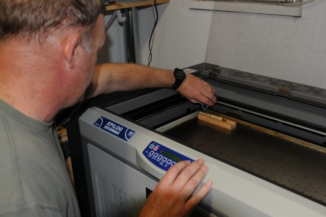 Demonstrating the laser engraver from his in-home woodshop, Chief Warrant Officer 4 Bill Noyer of the 166th Aviation Brigade, perfectly lines up a pen before engraving a sample product. (Photo by 1st Lt. Kat Kaliski, 166th Aviation Brigade, Division West, Public Affairs)