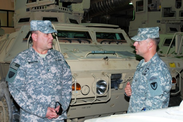 Col. John D. Kuenzli, commander, 402nd Army Field Support Brigade, briefs Brig. Gen. John Wharton, commanding general, Army Sustainment Command, while touring the warehouses at Camp Arifjan, Kuwait, April 18. (Photo by Johnnie Frazier, 402nd AFSB Public Affairs)