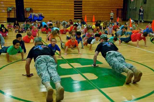 "Command Sgt. Maj. Carlos Gonzalezpabon and Lt. Col. Aaron West, the 1-290th Field Artillery Regiment command team demonstrate proper push up techniques for students at Southside Elementary School in Columbus, Ind. The Soldiers decided to adopt students at a local school for the  ""Let's Move"" campaign launched by First Lady Michelle Obama to combat childhood obesity to that list. (Photo by Capt. Olivia Cobiskey, 205th Infantry Brigade Public Affairs)"