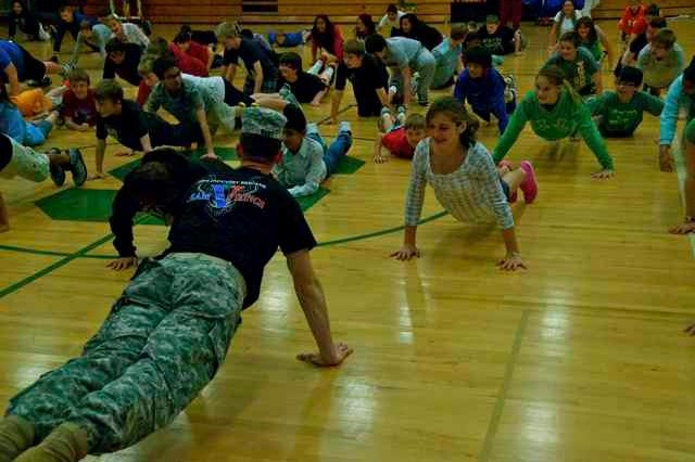 Lt. Col. Aaron West, commander of the 1-290th Field Artillery Regiment, demonstrates proper push up techniques for students at Southside Elementary School in Columbus, Ind. West decided to mentor local youth after hearing a statistic that 75 percent of America's youth are ineligible to join the military for a variety of reasons. Out of those ineligible, 17 percent are disqualified because of obesity. (Photo by Capt. Olivia Cobiskey, 205th Infantry Brigade Public Affairs)
