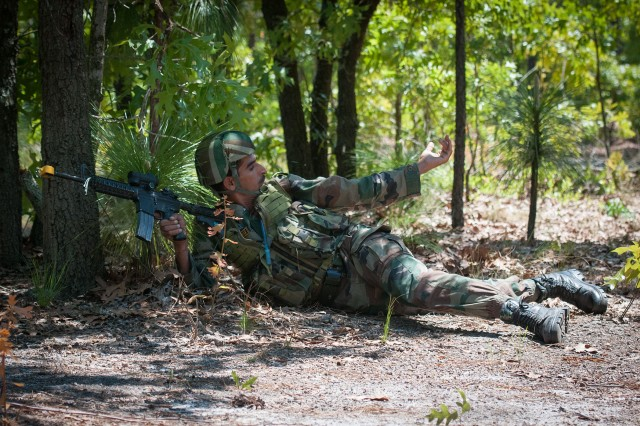 An Indian Army paratrooper with the 50th Independent Para Brigade signals to other soldiers to advance as they surround a mock village during field training with the 82nd Airborne Division's 1st Brigade Combat Team May 14, 2013, at Fort Bragg, N.C.  The training is part of Yudh Abhyas, annual bilateral training between the Indian Army and United States Army Pacific, hosted this year by the XVIII Airborne Corps at Fort Bragg.  (U.S. Army photo by Sgt. Michael J. MacLeod)