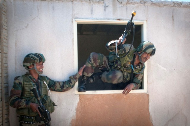 An Indian Army paratrooper with the 50th Independent Para Brigade climbs through the window of an mock insurgent compound during a company-level field exercise with U.S. Army paratroopers of the 82nd Airborne Division's 1st Brigade Combat Team May 14, 2013, at Fort Bragg, N.C.  The training is part of Yudh Abhyas, annual bilateral training between the Indian Army and United States Army Pacific, hosted this year by the XVIII Airborne Corps at Fort Bragg.  (U.S. Army photo by Sgt. Michael J. MacLeod)