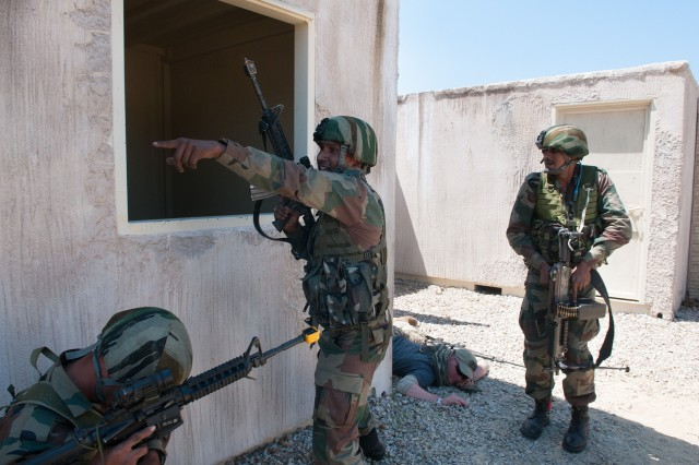 An Indian Army paratrooper with the 50th Independent Para Brigade gives direction to other soldiers while clearing a mock insurgent compound during field training with U.S. Army paratroopers with the 82nd Airborne Division's 1st Brigade Combat Team May 14, 2013, at Fort Bragg, N.C.  The training is part of Yudh Abhyas, annual bilateral training between the Indian Army and United States Army Pacific, hosted this year by the XVIII Airborne Corps at Fort Bragg.  (U.S. Army photo by Sgt. Michael J. MacLeod)