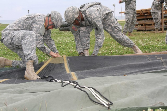 U.S. Soldiers with the 10th Regional Support Group work together to set up tents for a command post exercise at Torii Station in Okinawa, Japan, April 1, 2013. The exercise tested the unit's capabilities to provide command and control in response to a mock humanitarian aid mission.  (U.S. Army photo by Capt. Sonie Munson/Released)