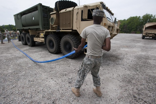 "Sgt. William White, 741st Quartermaster Company, South Carolina National Guard, carries a hose from the tactical water purification system to fill a water supply tank ""Hippo,"" Barnwell, S.C., May 18, 2013. The unit is participating in a major NORAD and USNORTHCOM sponsored training exercise called Ardent Sentry, May 17-21, 2013."