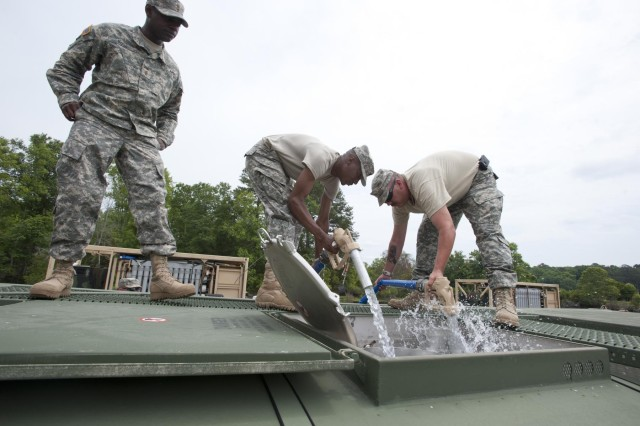 "2nd Lt. Anthony Ross observes Sgt. William White and Sgt. James Peeples, 741st Quartermaster Company, South Carolina National Guard, dispense purified water from a tactical water purification system into ""Hippo"" water supply tank, Barnwell, S.C., May 18, 2013. The unit is participating in a major NORAD and USNORTHCOM sponsored training exercise called Ardent Sentry, May 17-21, 2013."