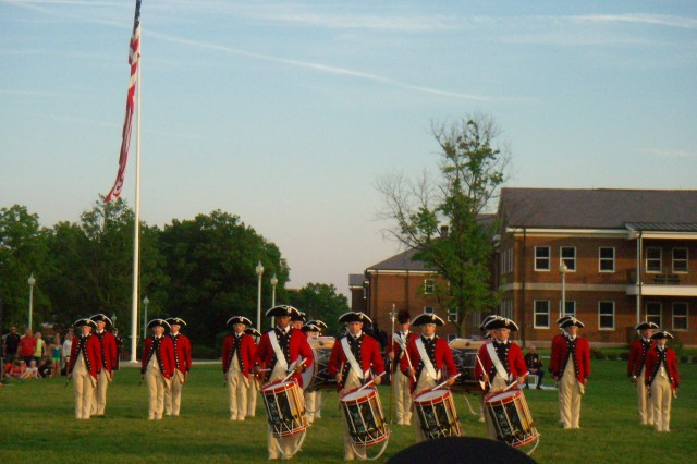 The Old Guard's Fife and Drum Corps, dressed in Revolutionary War-era uniforms, marches onto the parade ground during Twilight Tattoo at Joint Base Myer-Henderson Hall.