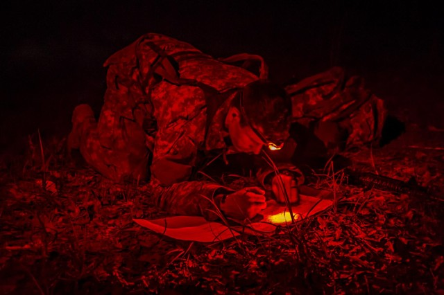 """Sgt. Ryan Thaxton, a native of Savannah, Ga., and a team leader for Company A, 1st Battalion, 64th Armor Regiment """"Battlekings"""", 2nd Armored Brigade Combat Team, 3rd Infantry Division, plots points on a map by red light in the pitch black of night before steeping out on a graded land navigation course which was part of his assessment during the 2nd ABCT's first Pre-Ranger course here April, 24. He is on his second from last day of his assessment, which was over a month long. The course started with 16 candidates but only two others made it as far as Thaxton did that day. The course is designed to prepare and to ascertain readiness of soldiers wishing to attend Ranger School. Right now the Army is experiencing a shortage of Rangers, and the founders of this program are hoping that it will increase the successful pass rate of Spartans wanting to go to Ranger School.  (U.S. Army photo by Sgt. Richard Wrigley, 2nd ABCT, 3rd ID, Public Affairs NCO)"""