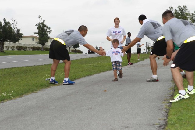 Soldiers from 10th Regional Support Group give high fives to a participant in the America's Armed Forces Kids Run held May 18 at Kadena Air Base. This year more than 200 participants ran in the annual race in celebration of Armed Forces Day.