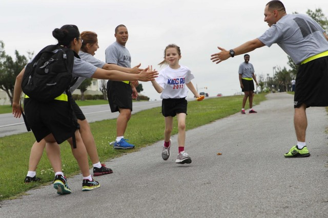Soldiers from 10th Regional Support Group give high fives to a participant in the America's Armed Forces Kids Run held on May18 at Kadena Air Base. This year more than 200 participants ran in the annual race in celebration of Armed Forces Day.