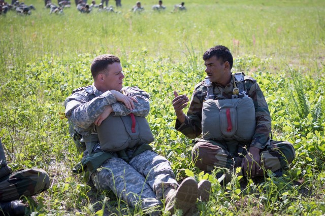 Indian and U.S. Army paratroopers chat while waiting for CH47 Chinook helicopters to pick them up for an airborne operation May 15, 2013, at Fort Bragg, N.C.  The paratroopers are assigned to the Indian Army 50th Independent Para Brigade and the U.S. Army, 82nd Airborne Division's 1st Brigade Combat Team.  (U.S. Army photo by Sgt. Michael J. MacLeod)