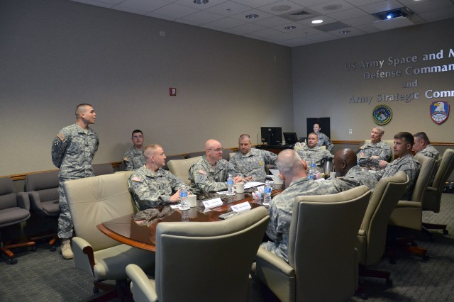 Staff Sgt. Oscar A. Perez, an intelligence analyst, 2nd Space Company, 1st Space Battalion, far left, leads off the brief to Sgt. Maj. of the Army Raymond F. Chandler III during a visit to the U.S. Army Space and Missile Defense Command/Army Forces Strategic Command Operations headquarters, Peterson Air Force Base, Colo., on May 15. This update provided Chandler with an insight on the latest space-based capabilities Army Space Soldiers provide the Warfighter.