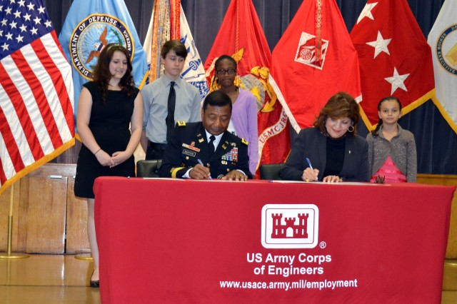 Lt. Gen. Thomas Bostick, U.S. Army Corps of Engineers commanding general, and Marilee Fitzgerald, DoDEA director, sign the memorandum of understanding while Quantico elementary and middle school students watch.