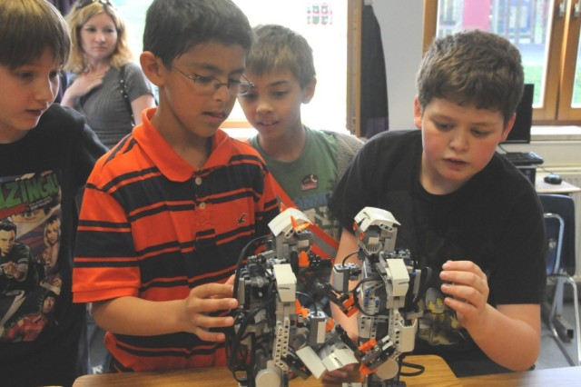 A group of students exam a pair of robots programmed to battle one another at the HES STEAM event.