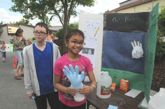 "Ethan Field and Kayana Taitano demonstrate a chemical reaction to create ""The Hand,"" at the HES STEAM event."