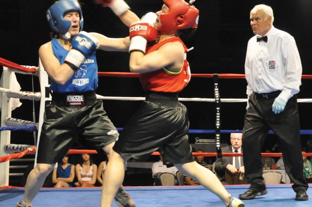 Ring official Thomas Hlavacek looks on as Wiesbaden's Lisa Manela and Alicia Demilio mix it up at the U.S. Forces Europe Boxing Championships in Wiesbaden May 11. Manela was crowned the champ after a close decision.