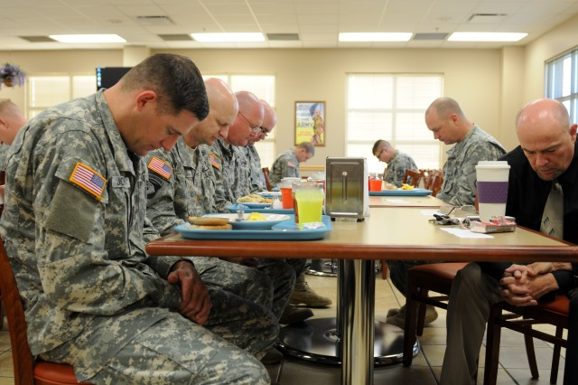 Soldiers from the 3d ESC bow during a prayer given at a prayer breakfast held 15 May here at Cantigny Dining Facility. The prayer breakfast was themed around learning to be content with the changes in the Army.(U.S. Army photo by Staff Sgt. Candice L. Funchess)