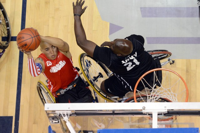 Marine veteran Cpl. Josue Barron puts up a shot over Army's Perry Price during the gold medal wheelchair basketball match of the 2013 Warrior Games in Colorado Springs, Colo., May 15, 2013. Army won the gold.