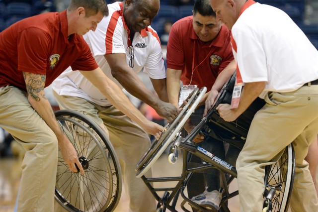 Marine coaches and trainers try replace a broken wheel on a wheelchair with Marine Sgt. Eric Rodriguez still sitting in it during the wheelchair basketball gold medal match of the 2013 Warrior Games in Colorado Springs, Colo., May 15, 2013.