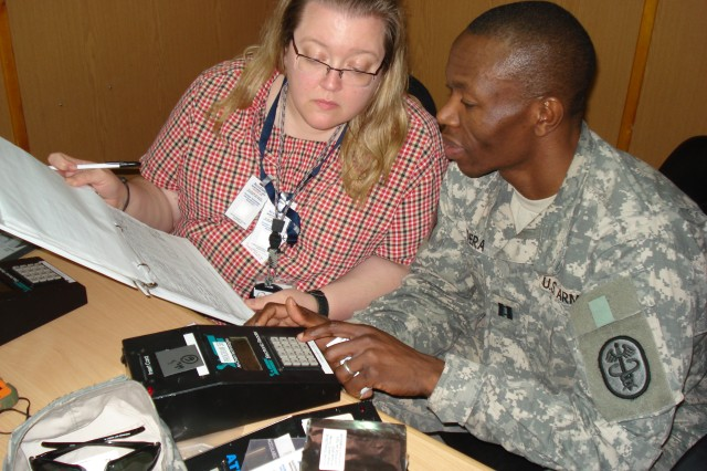 "Jennifer Mancini, an industrial hygienist from USAPHC, Aberdeen Proving Ground, Md., and Capt. Ayub Odera, an environmental science and engineering officer at Public Heath Command Region"" North, read and record results from a personal monitoring card."
