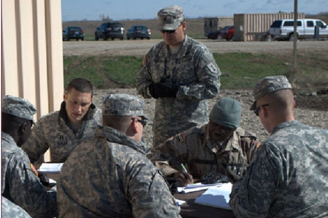 "Soldiers with 2nd Armored Brigade Combat Team ""Dagger,"" 1st Infantry Division, work with a role player acting as an African host nation security force Soldier (second from right), April 12, 2013, at Fort Riley, Kan., during the practical exercise portion of the six-day preparatory course known as ""Dagger University."" The course educates and tests Soldiers prior to their deployment in support of the brigade's regional alignment with Africa."