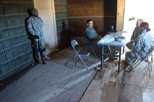 "First Lt. Deseret Fournier (right), platoon leader, and Sgt. 1st Class Travis McIvor (second from right), platoon sergeant, both with Headquarters and Headquarters Company, Special Troops Battalion, 2nd Armored Brigade Combat Team ""Dagger,"" 1st Infantry Division, work with a role player acting as an African host nation security force Soldier, April 12, 2013, at Fort Riley, Kan., during the practical exercise portion of the six-day preparatory course known as ""Dagger University."" The course educates and tests Soldiers prior to their deployment in support of the brigade's regional alignment with Africa."
