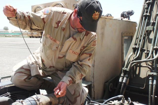 Chris Flegel, a TACOM Automotive logistics assistance representative, checks oil on a vehicle at FOB Salerno, Afghanistan, May 17. (Photo by Graydon Field, Brigade Logistics Support Team)