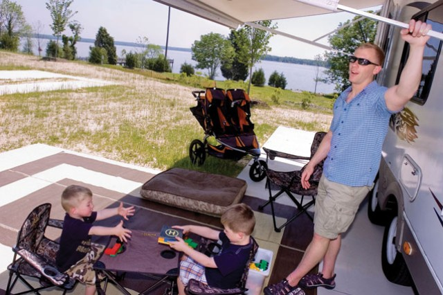 Brothers Roderick, 2, left, and Abraham Allgeyer, 4, begin to pull out their toys with their father Jesse Allgeyer at the new Fort Belvoir Travel Camp Friday. Allgeyer has been stationed to an installation in the area, and he, his sons; wife, Briita; infant daughter, Penelope; and dog, Bjorn, moved from Washington state with their RV.