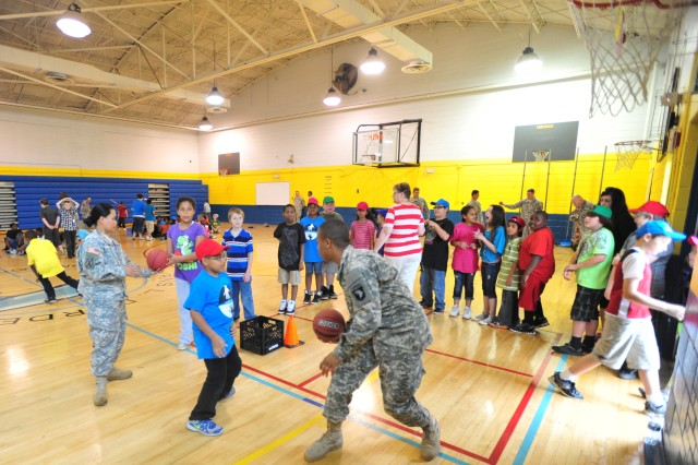 "FORT CAMPBELL, Ky""U.S. Army Staff Sgt. Florgely Britton, a food service specialist, and Pvt. Quamaine Ward, an automated logistical specialist, with 801st Brigade Support Battalion, 4th Brigade Combat Team, 101st Airborne Division, play basketball with Byrens Darden Elementary School students, May 17, 2013, during the school's field day at Clarksville, Tn. (U.S. Army photo by Sgt. Kimberly K. Menzies, 4th Brigade Combat Team Public Affairs)"