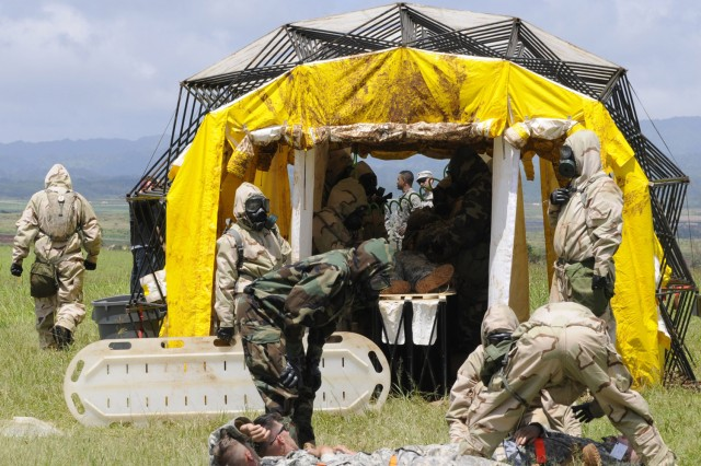 Soldiers from the 71st Chemical Company, 8th Military Police Brigade load role-playing patients onto litters to be treated in a mass casualty decontamination shelter during a Consequence Management Exercise, April 25.