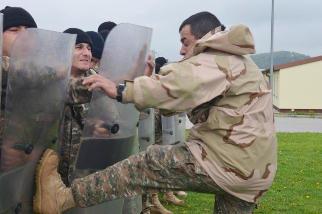 An Armenian soldier plants a boot against a fellow soldier's riot shield as a part of crowd and riot control training May 4 at the Joint Multinational Readiness Center at Hohenfels, Germany. The multinational training event is in preparation for the 525th Battlefield Surveillance Brigade's upcoming deployment to Kosovo, where U.S. soldiers will be working with a multinational force as a part of KFOR.