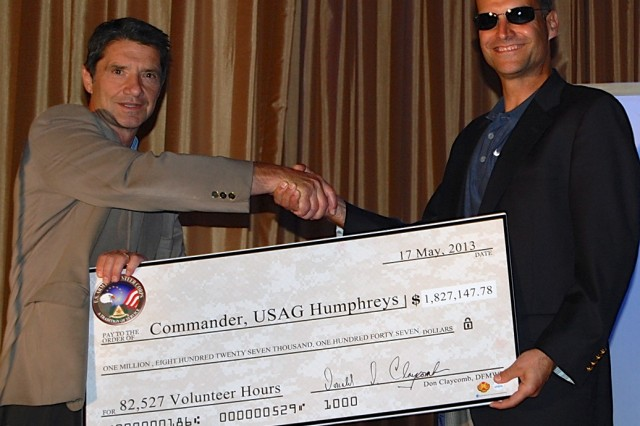 Donald Claycomb, the Humphreys Family and Morale, Welfare and Recreation director, presents Col. Darin S. Conkright, Humphreys Garrison commander, with a ceremonial check for $1,827,147.78, representing the total savings volunteers contribute to the community.