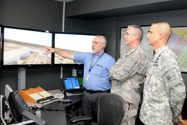 Joe White, Directorate of Plans, Training, Mobilization and Security Aviation Division chief, shows Brig. Gen. Timothy Edens, commanding general of the U.S. Army Combat Readiness / Safety Center and director of Army Safety, and Command Sgt. Maj. Richard Stidley, USACR / Safety Center senior enlisted adviser, the state-of-the-army air traffic control simulator Tuesday at Wheeler-Sack Army Airfield.