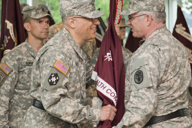 Maj. Gen. Dean G. Sienko (center) accepts the USAPHC's colors from Maj. Gen. Richard A. Stone, deputy Army surgeon general (right). Cmd. Sgt. Major Gerald C. Ecker, at left, stands before the USAPHC color guard. Sienko is the 4th commander to lead the USAPHC